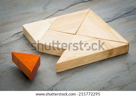 a missing piece in a square built from tangram shapes, a traditional Chinese puzzle game, slate rock background - stock photo