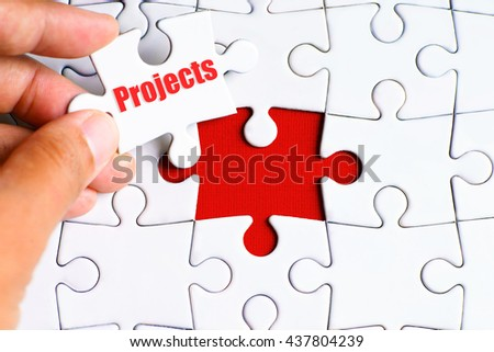"""A missing puzzle with a hand hold a piece of """"Projects"""" text puzzle want to complete it - business and finance concept - stock photo"""