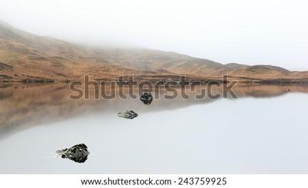 A mist covered Loch with mountain reflection near glencoe, scotland. - stock photo