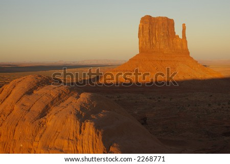 A mitten mesa lit up by the setting sun in Monument Valley park (Navajo Nation) with a boulder in the foreground. - stock photo