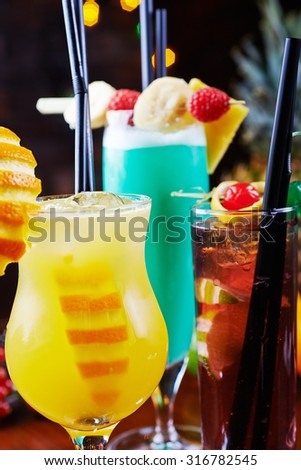 a mix of a few bright tropical cocktails or glasses of lemonade with slices of orange and beautiful decoration on a table in a restaurant with backgrounds of bright colored lights. soft focus. - stock photo