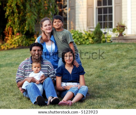 A mixed-race family of five on the lawn of their suburban home. - stock photo