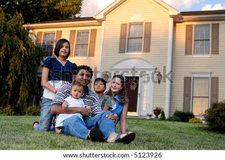 A mixed-race family of five with their suburban home behind them. - stock photo