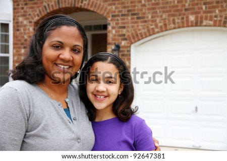 A mixed race mother and daughter at their home - stock photo
