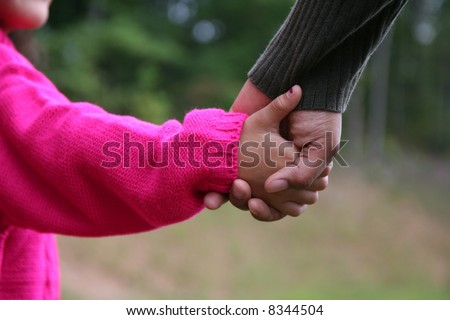 A mixed race mother and daughter holding hands - stock photo