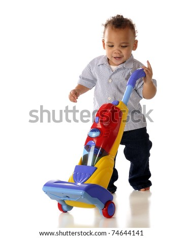 A mixed race toddler vacuuming with his toy vacuum cleaner.  Isolated on white. - stock photo