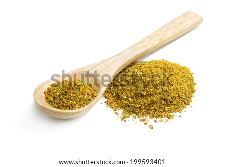 A mixture of ground spices with turmeric and cumin in a wooden spoon - stock photo