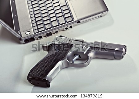 A 9mm handgun and  a laptop computer resting on a table. Backlit, shallow depth of field. - stock photo