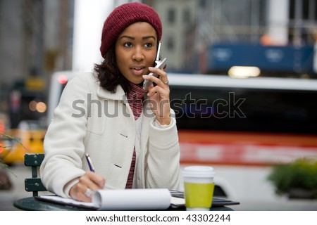A mobile business woman in the city talks on her cell phone while writing something down in her notepad. - stock photo