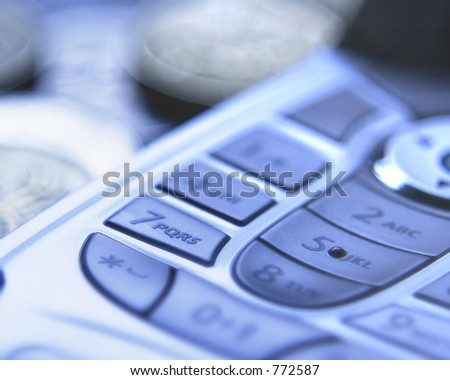 A Mobile phone with selective focus including blurred money in the background. Overall blue tint.