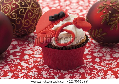 A mocha cupcake with decorations and icing on top surrounded by Christmas balls - stock photo