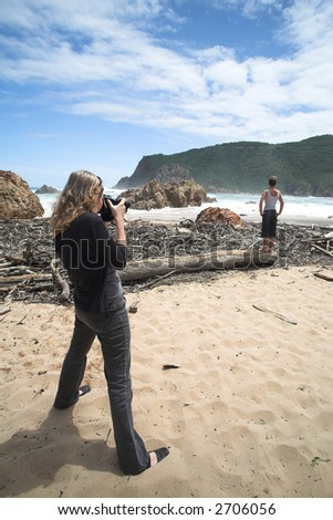A model being shot on the beach at The Heads in Knysna, Western Cape, South Africa. The Female model is standing on some driftwood and flotsam with crashing waves in the background. - stock photo