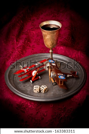 A model Fokker Triplane and a Sopwith Camel on a plate with wine goblet - stock photo