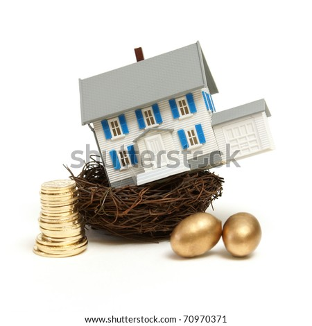 A model house rests in a nest with gold coins and eggs for many investment concepts.