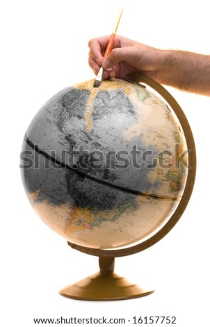 A model of the earth being painted as a symbolic way of showing someone brightening up the planet - stock photo