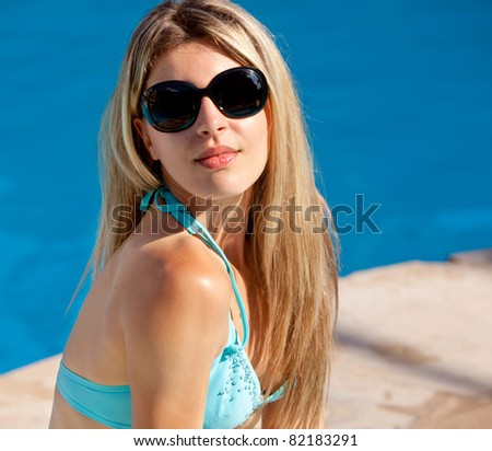 A model sitting beside a pool with sunglasses on - stock photo