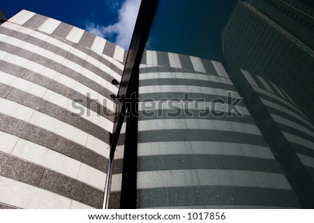 A moden-looking building is reflected in a window with a deep blue sky in the background - stock photo