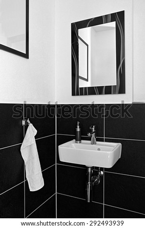 A modern bathroom sink and mirror with hand towel, held in black an white. - stock photo