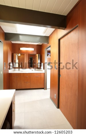 A modern bathroom with two sinks and dark wood walls