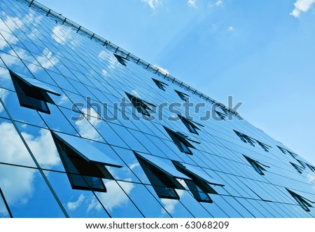 A modern building with mirrored windows reflecting the blue sky.