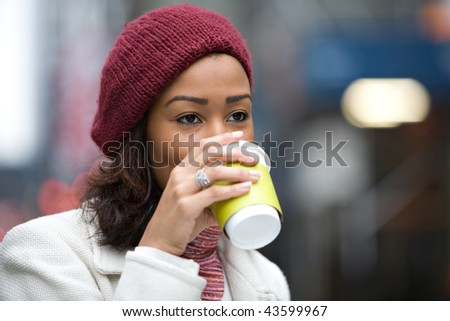 A modern business woman in the city  enjoying a cup of coffee hot chocolate latte or tea. - stock photo