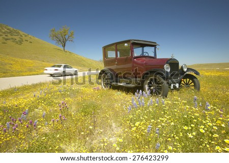 A modern car driving by a maroon Model T parked alongside a scenic road surrounded by spring flowers,  Route 58, Shell Road, CA - stock photo