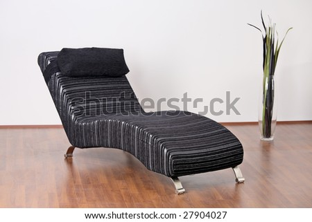 A modern chair and a vase - stock photo