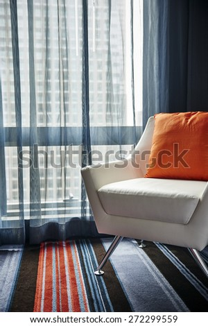 a modern chair in a room next to a window - stock photo