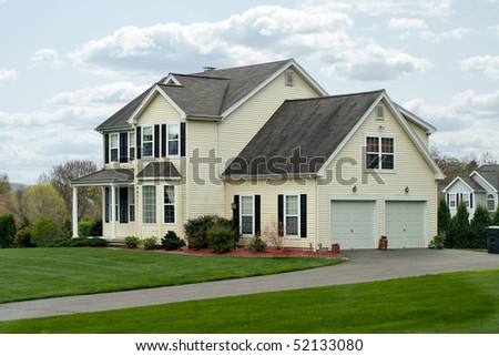 A modern colonial style residential suburban home with a small porch and a two car garage. - stock photo