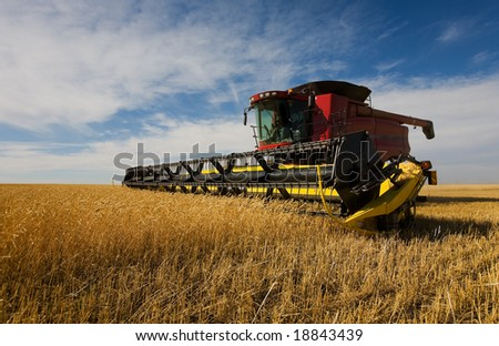 A modern combine harvester working on a wheat crop - stock photo