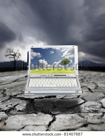 A modern computer laptop showing a tree growing on a fertile green field with cloudy blue sky on its screen, in contrast to a drought stricken arid landscape with a dying tree due to global warming. - stock photo
