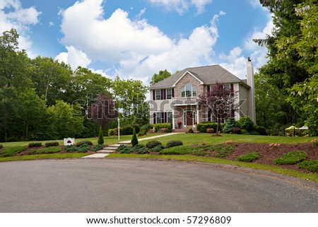 A modern custom built luxury home in a residential cul-de-sac neighborhood.  This high end house is very nicely landscaped property. - stock photo