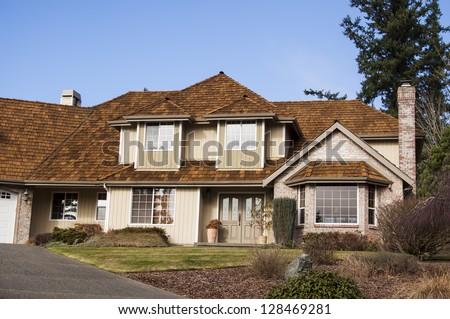 A modern custom built luxury home in a residential neighborhood. - stock photo