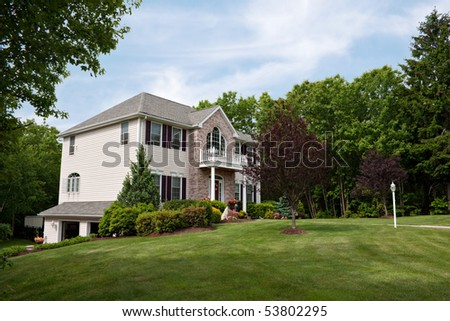 A modern custom built luxury home with a two car garage in a residential neighborhood.  This high end house is very nicely landscaped property. - stock photo