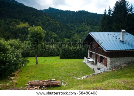 A modern environmentally friendly chalet equipped with solar panels in the forests surrounding by mountains of the French Alps near Albertville, France. Horizontal