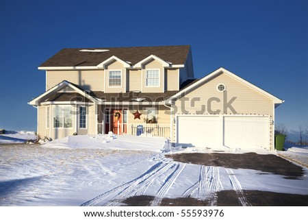 A modern family home decorated for Christmas and in a snowy landscape. - stock photo