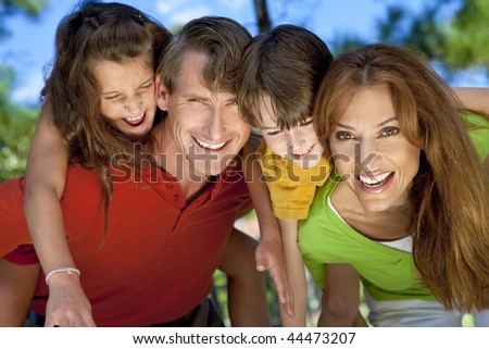 A modern family of father, mother, daughter and son playing together and having doing piggy back in a park - stock photo