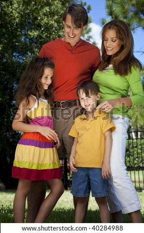 A modern family of father, mother, daughter and son playing together and having fun in a park. - stock photo