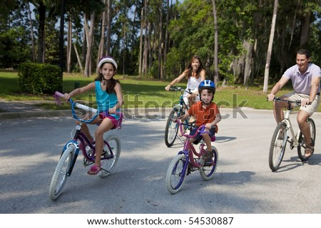 A modern family of two parents and two children, a boy and a girl, cycling together. - stock photo