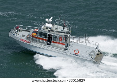 A modern fireboat moving at speed. - stock photo