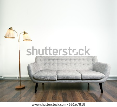 A modern gray sofa and a retro lamp with two heads against bright background on wooden floor - stock photo