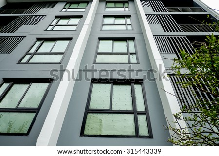 A modern high rise condominium tower rising into a clear blue sky   - stock photo