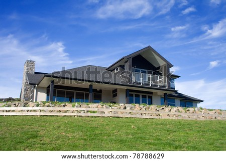 A modern home exterior positioned on a hill top with vibrant blue skies - stock photo