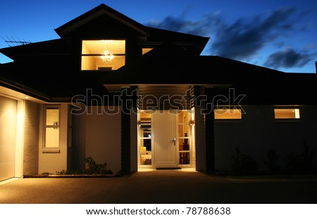 A modern house front entrance at night - stock photo