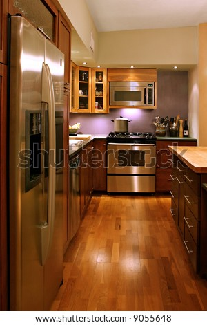 A modern kitchen with stainless steel appliances, slate countertops and handmade wooden cabinets,