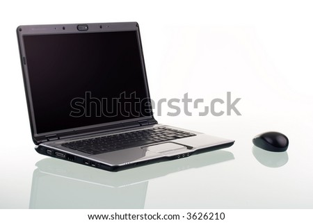 A modern laptop computer and wireless mouse with reflection on a glass surface. - stock photo