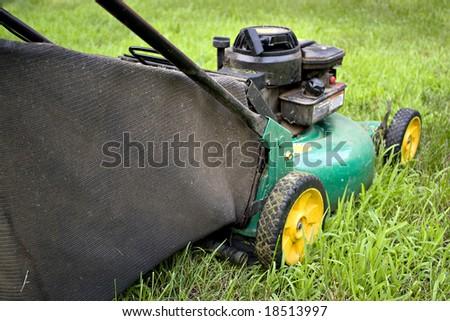 A modern lawn mower cutting through the grass. - stock photo