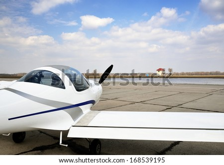 A modern light plane is on the aerodrome against the sky.