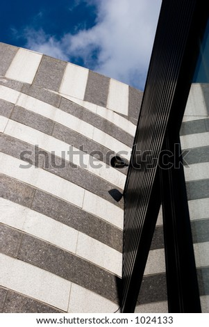 A modern-looking building is reflected in a window with a deep blue sky in the background - stock photo