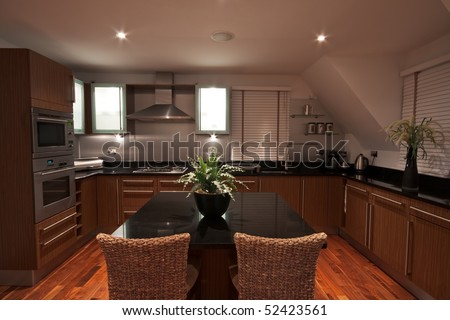 A modern luxurious kitchen area with marble surfaces, wooden flooring, and stainless steel appliances. - stock photo